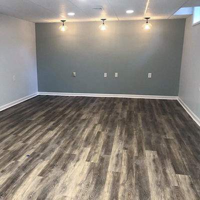 modern basement renovation with accent paint and lighting with LVT